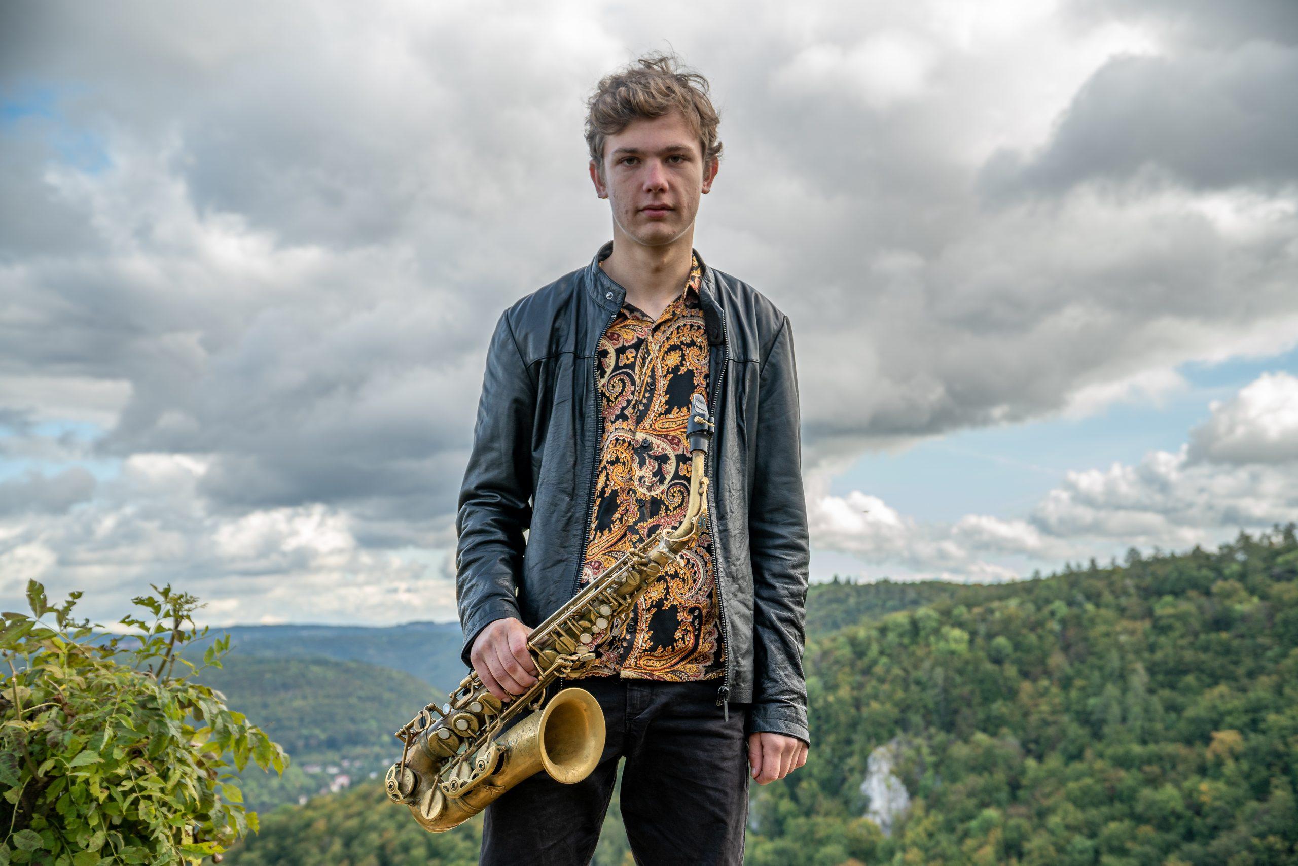 Jakob Manz mit Saxophon vor dem Panorama der schwäbischen Alb